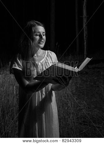 Monochrome Portrait Of Woman Holding Big Old Book At Night Forest