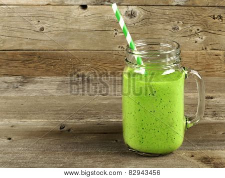Green smoothie on old wood background