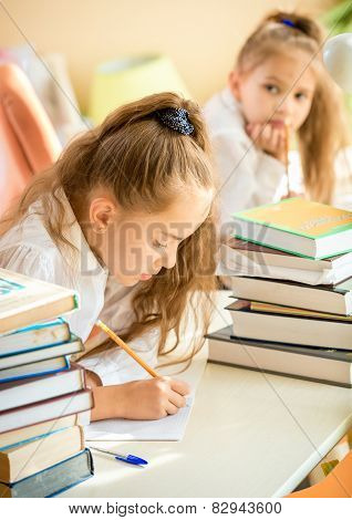 Concentrated Girl Doing Homework While Classmate Trying To Write Off