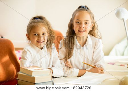 Two Classmates Sitting At Desk And Smiling