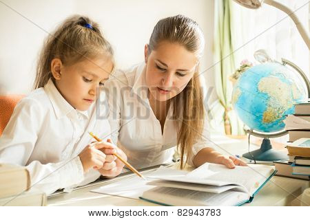 Mother Sitting With Daughter At Desk And Explaining Task At Homework
