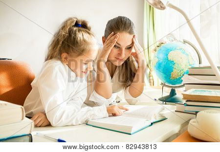 Confused Mother Looking At Daughters Complicated Homework