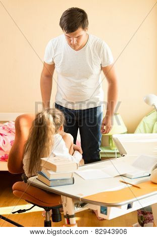 Father Looking With Fierce At Intimidated Daughter