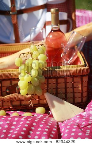 A beautiful Picnic Basket featuring fresh Green Grapes, Wine, Bread and Cheese. Selective focus with a shallow depth of field for a 3-D effect. Focus is on grapes.