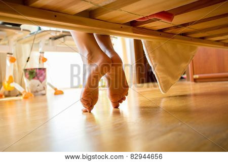 Closeup Shot Of Female Feet Under Bed