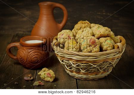 Cookies in a basket, a clay jug and a cup of milk