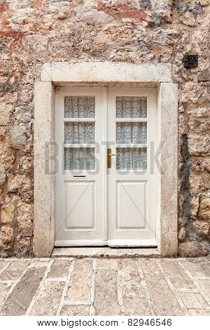 White Classic Door In Ancient Stone Building