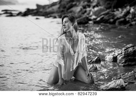 Monochrome Photo Of Sexy Young Woman Kneeling At Sea Shore