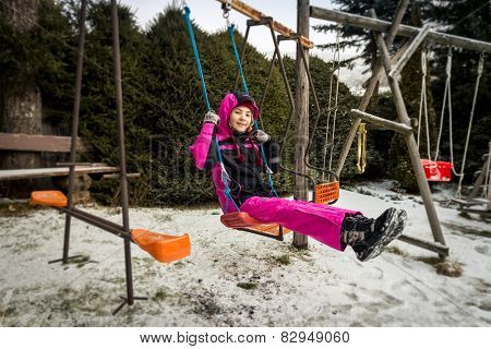 Smiling Girl Riding On Swing On Playground At Snowy Day