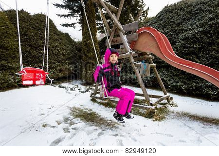 Little Girl Swinging On Playground At Cold Snowy Day