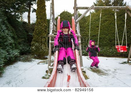 Two Little Girls Having Fun On Playground At Cold Snowy Day
