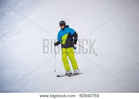 Skier Riding The Downhill On Ski Resort