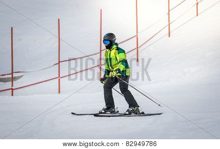 Man In Green Suit Skiing Down The Hill