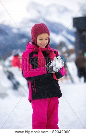 Smiling Girl Posing Against High Mountains With Snowball