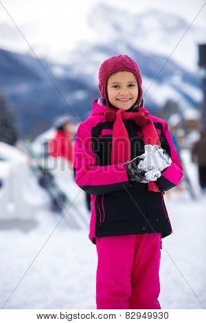 Smiling Girl In Pink Ski Suit Making Snowball