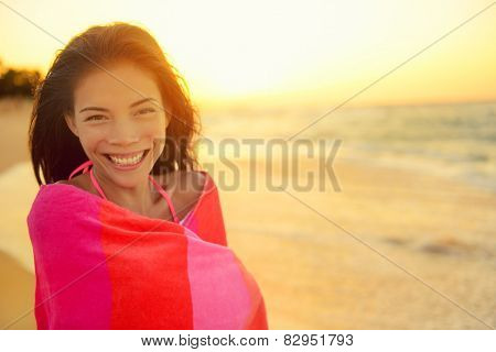Young pretty mixed race Asian Caucasian model woman wrapped in towel standing in beach sunset. Smiling happy enjoying summer holiday travel vacation. Hawaii.