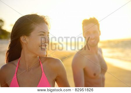 Joyful young mixed race couple on beach sunset enjoying summer vacation holiday travel. Beautiful smiling Asian woman, young pretty Caucasian male. Hawaii.