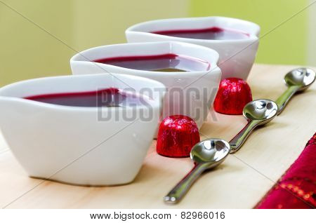 Strawberry jam (sweet) in a pot on wooden table with candies in wrapper, tablespoons and green backg