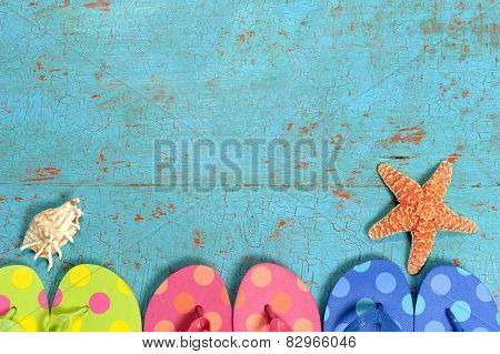 Summer concept with flip flops of different colors, starfish and shell over grunge table