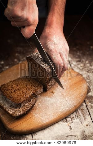 Male Hands Slicing Fresh Bread On Table