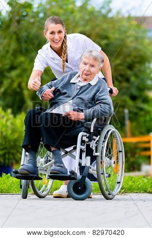 Senior woman in nursing home with nurse in garden sitting in wheelchair giving the thumbs up sign