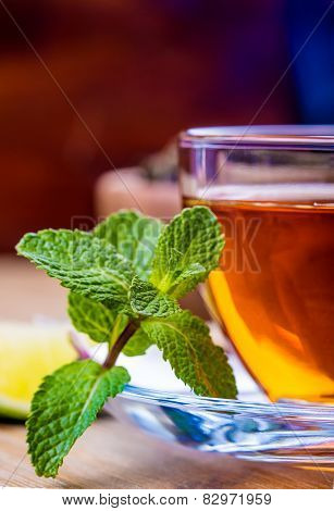 Tea in a glass cup, mint leaves, dried tea, sliced lime, cane sugar