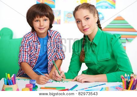 Little boy and teacher drawing in a preschool center