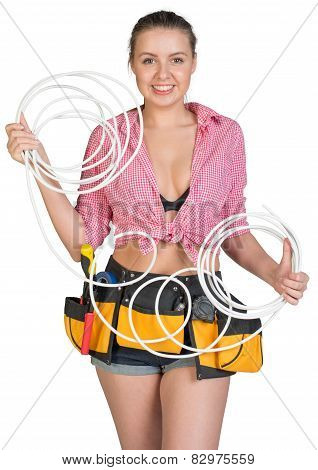 Sexy woman in hard hat and tool belt holding coil of cable