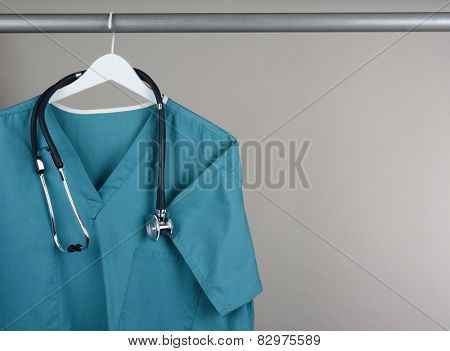 Closeup of a doctor's scrubs and stethoscope on hanger against a neutral background. Green surgical smock on a white hanger with a gray background with copy space.