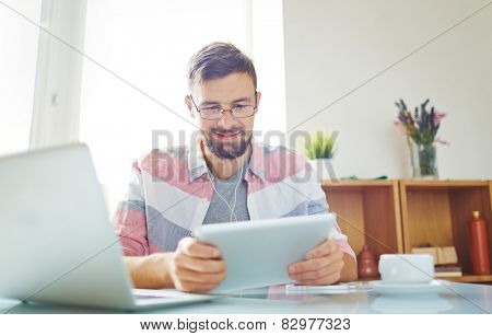 Businessman in casual working with modern gadgets in office