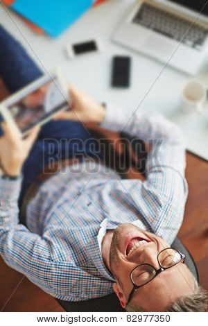 Ecstatic businessman with touchpad laughing at workplace