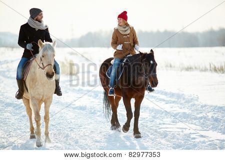 Happy couple in winterwear horse riding in natural environment