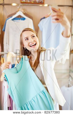 Beautiful young woman with new dress making selfie in department store