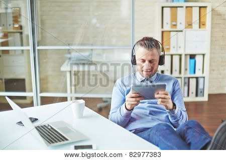 Happy businessman with earphones and touchpad having break in office