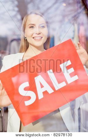Beautiful young woman announcing season sale in boutique