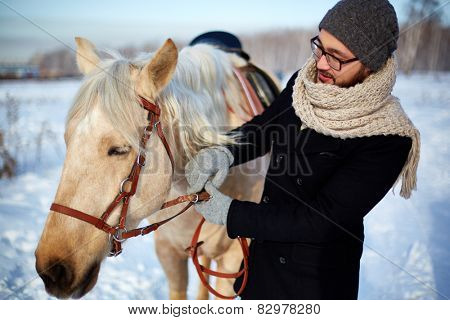 Young man in winterwear looking at horse outdoors