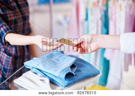Shopper hand giving plastic card to shop assistant
