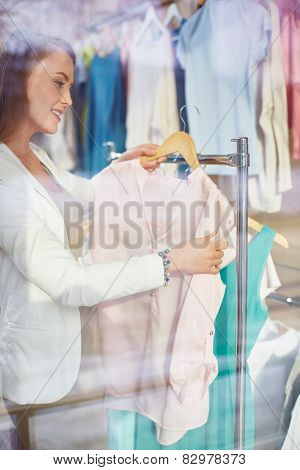 Beautiful woman looking through new clothes collection in boutique