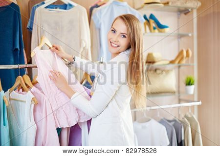 Beautiful young woman in clothing department