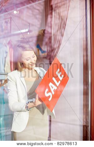 Beautiful shop assistant putting sale card on door of boutique