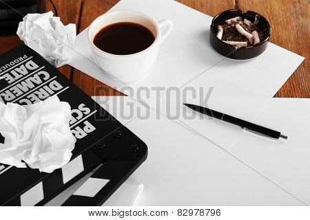 Moving clapper with sheets of paper, ashtray, cup of coffee and pen on wooden planks background
