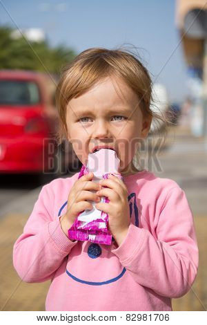 Adorable Little Girl Eating An Ice Cream Outdoors