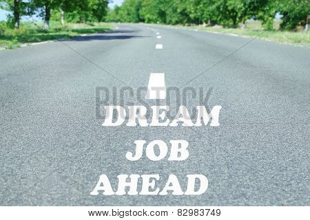 Text Dream Job Ahead marking on road surface