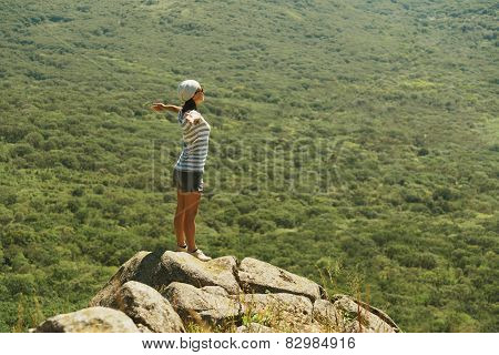 Woman Standing With Raised Arms On Peak Of Rock In Summer