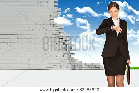 Businesswoman holding suitcase and looking at watch. Dilapidated brick wall, green meadow with sky a
