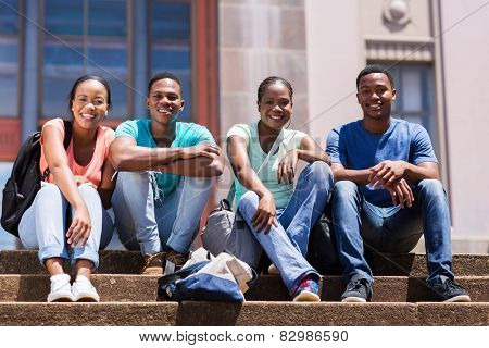 group of happy african student sitting outside college building