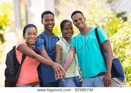 group of cheerful african college students putting hands together