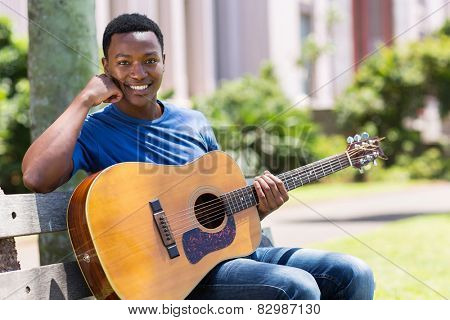 portrait of handsome african college student with a guitar outdoors