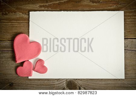 White Paper With Small Pink Hearts Lying On A Wooden Background