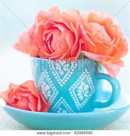 roses in a blue cup
